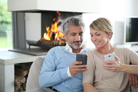 homeowners looking at their phones by the fire